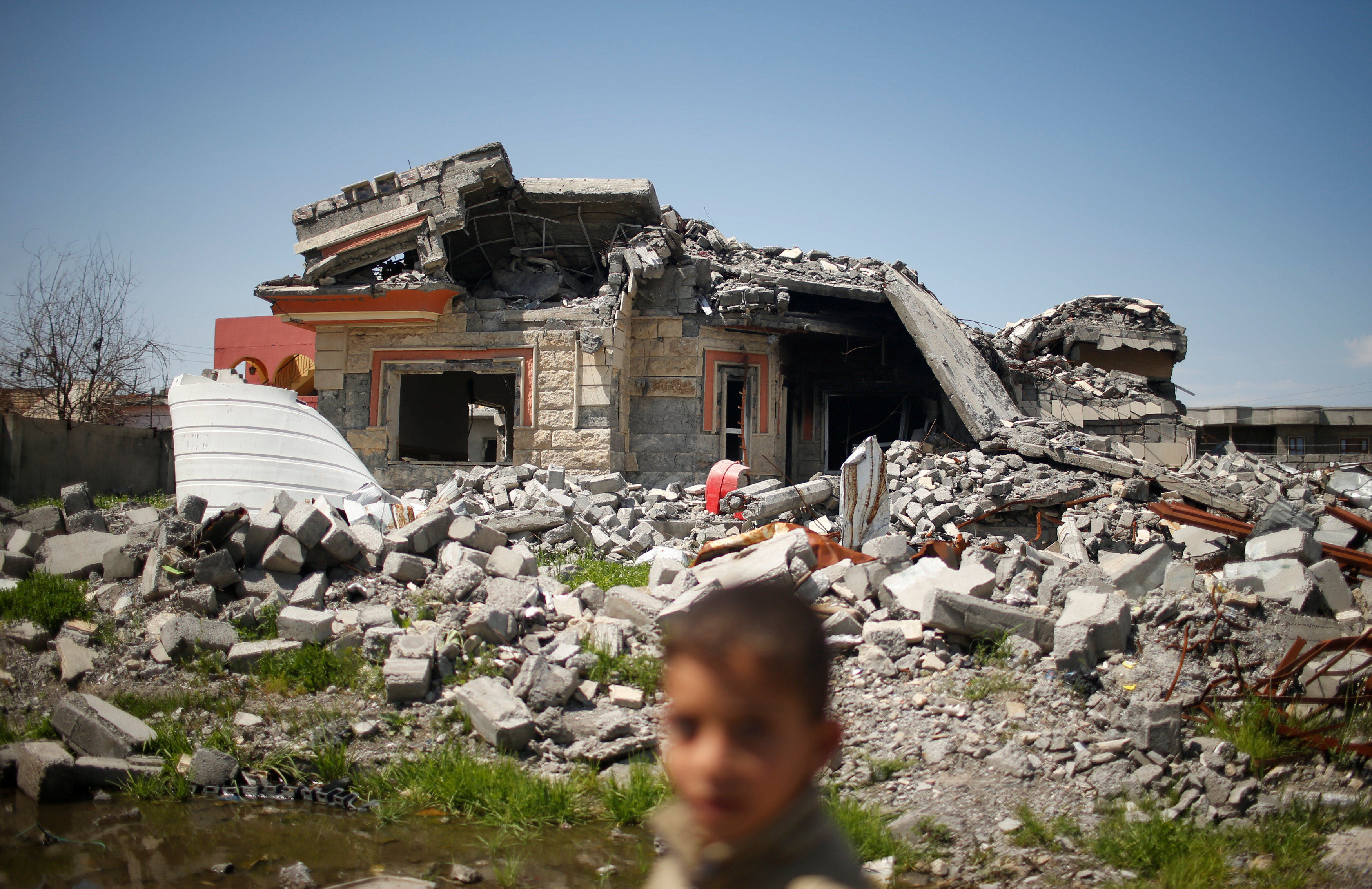 An Iraqi boy walks past a building destroyed during the fighting between Iraqi forces and Islamic states militants in Qayyara,