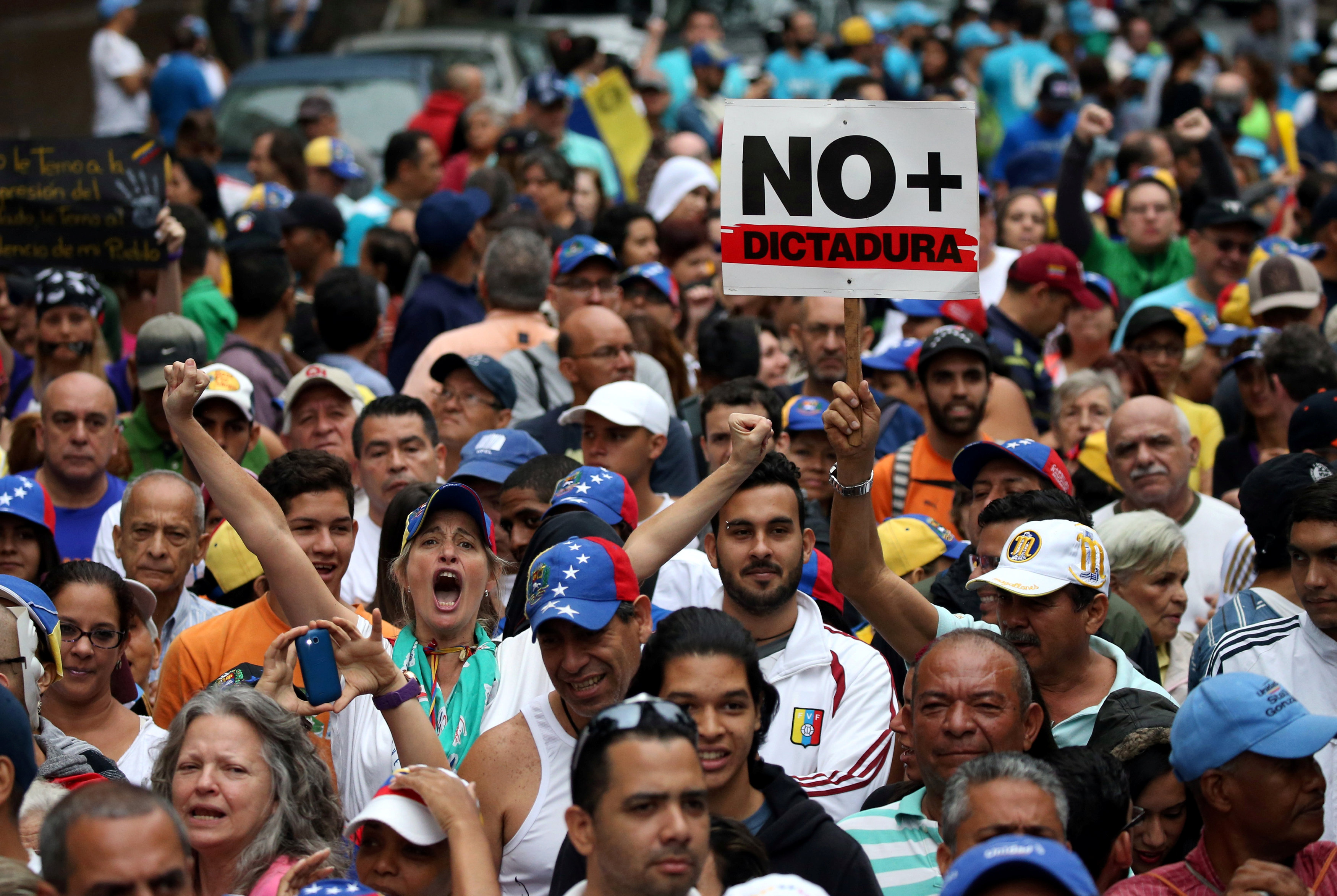 "Demonstrators rally against Venezuela's President Nicolas Maduro carrying a sign that reads ""No more dictatorship"" in Caracas, Venezuela, April 13, 2017. REUTERS/Carlos Garcia Rawlins"