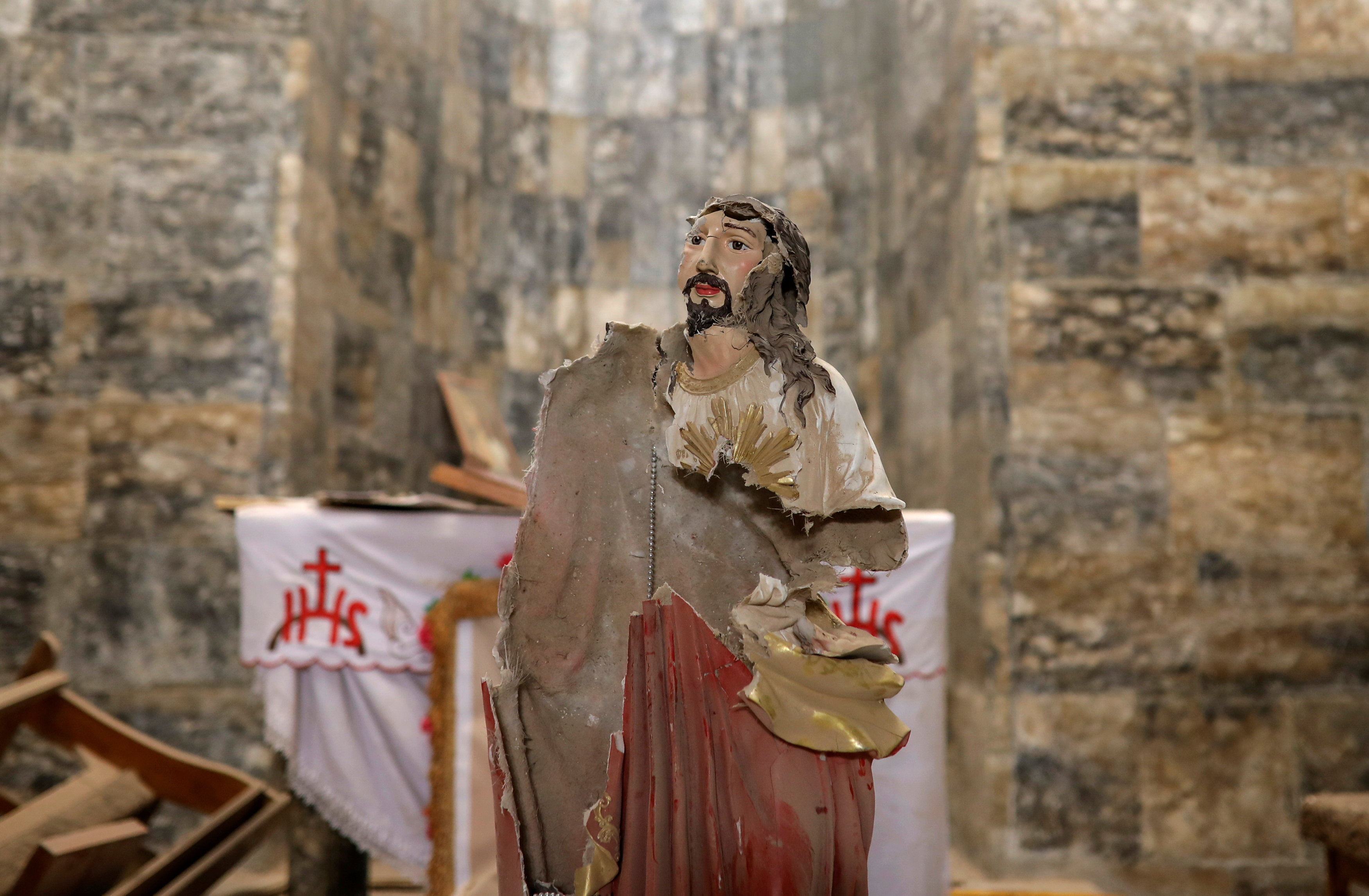 A damaged statue of Jesus Christ is seen inside a church in the town of Qaraqosh, south of Mosul, Iraq, April 11, 2017. REUTERS/Marko Djurica SEARCH