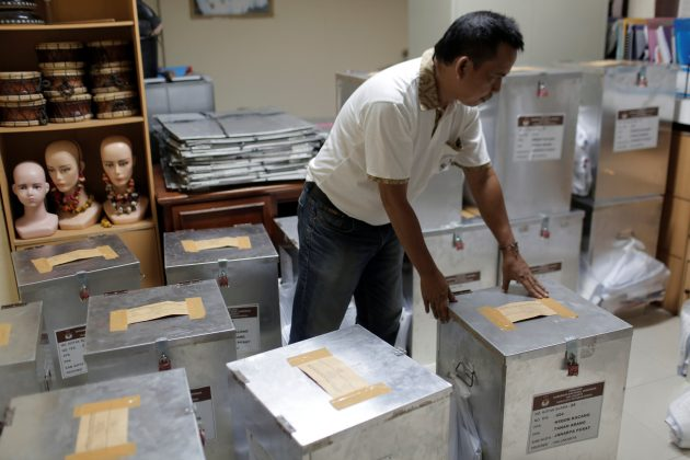 An election official prepares ballot boxes before distributing them to polling stations, in Jakarta, Indonesia April 18, 2017. REUTERS/Beawiharta