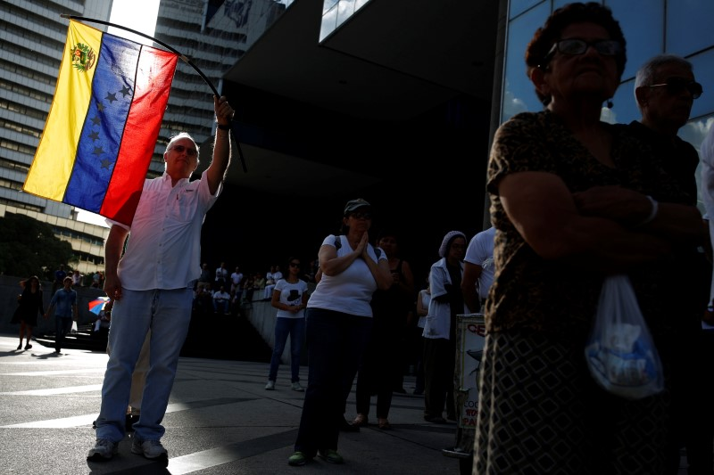 FILE PHOTO: An opposition supporter waves a Venezuelan flag during a gathering against Venezuela's President Nicolas Maduro's government in Caracas, Venezuela April 15, 2017. REUTERS/Carlos Garcia Rawlins