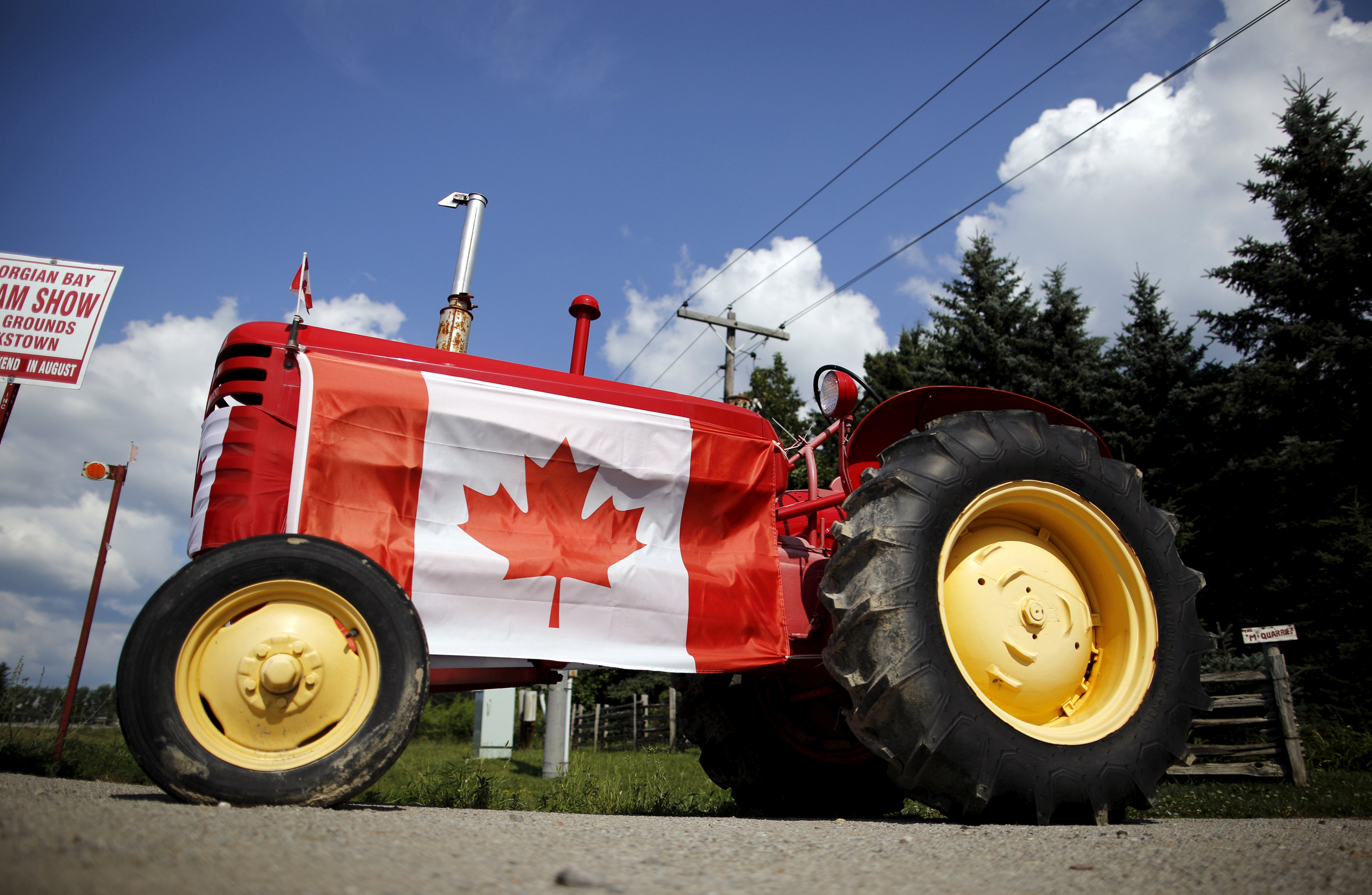 FILE PHOTO: An old tractor sporting a Canadian national flag is seen parked in the rural township of Oro-Medonte, Ontario July 26, 2015. REUTERS/Chris Helgren/File Photo