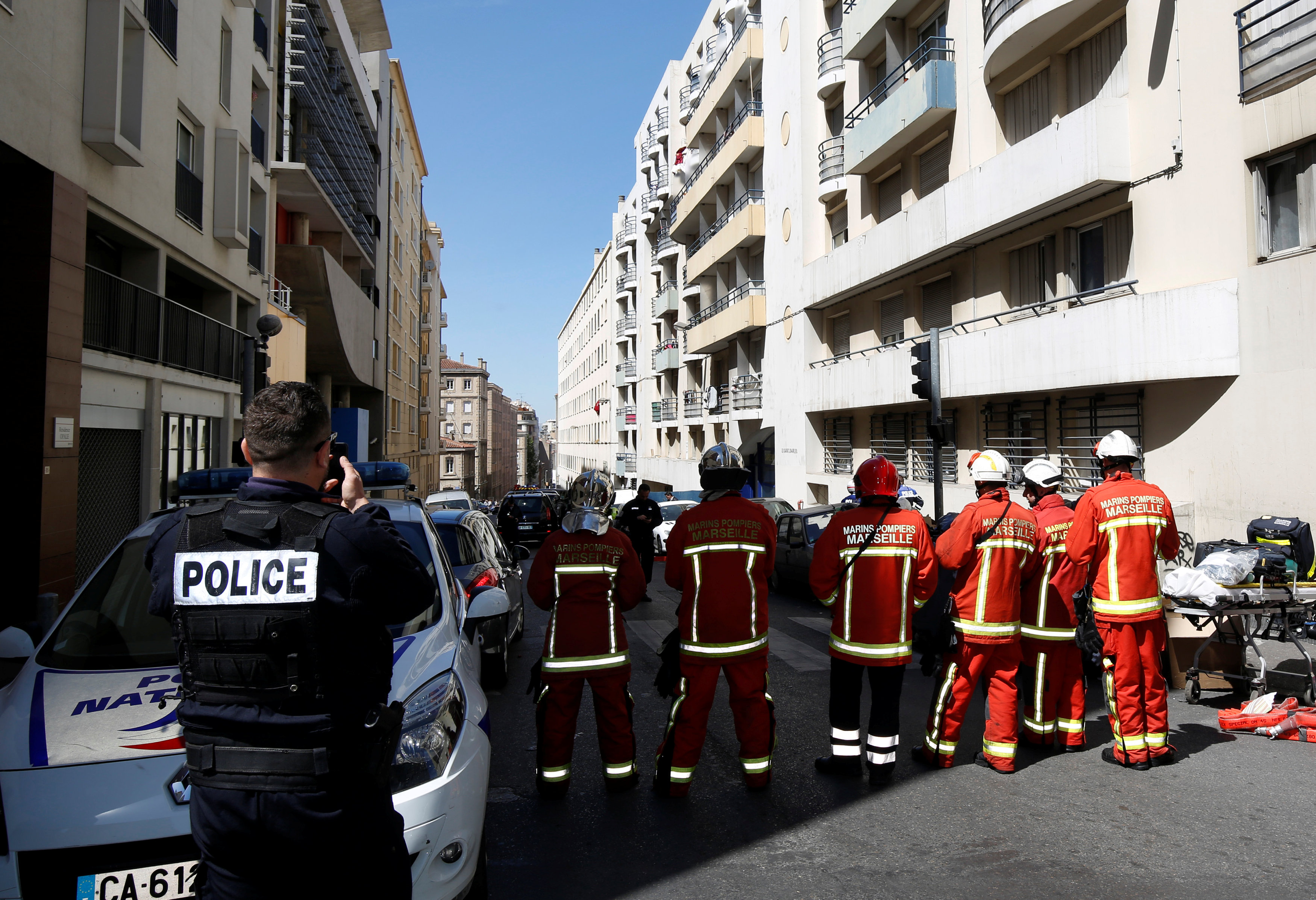 """French firefighters secure the street as police conduct an investigation after two Frenchmen were arrested in Marseille, France, April 18, 2017 for planning to carry out an """"imminent and violent attack"""" ahead of the first round of the presidential election on Sunday, France's interior minister said. REUTERS/Philippe Laurenson"""