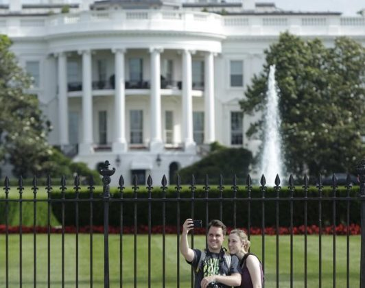 Tourists take selfies by the original South Lawn security fencing at the White House in Washington May 28, 2015. REUTERS/Gary Cameron