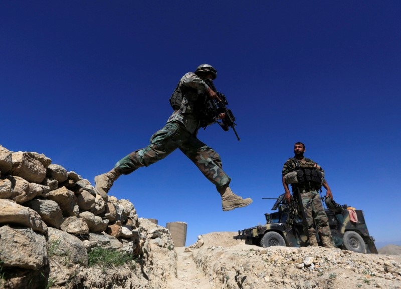 A member of Afghanistan's Special Forces unit jumps from a wall during patrol in Pandola village near the site of a U.S. bombing in the Achin district of Nangarhar, eastern Afghanistan, April 14, 2017. REUTERS/Parwiz