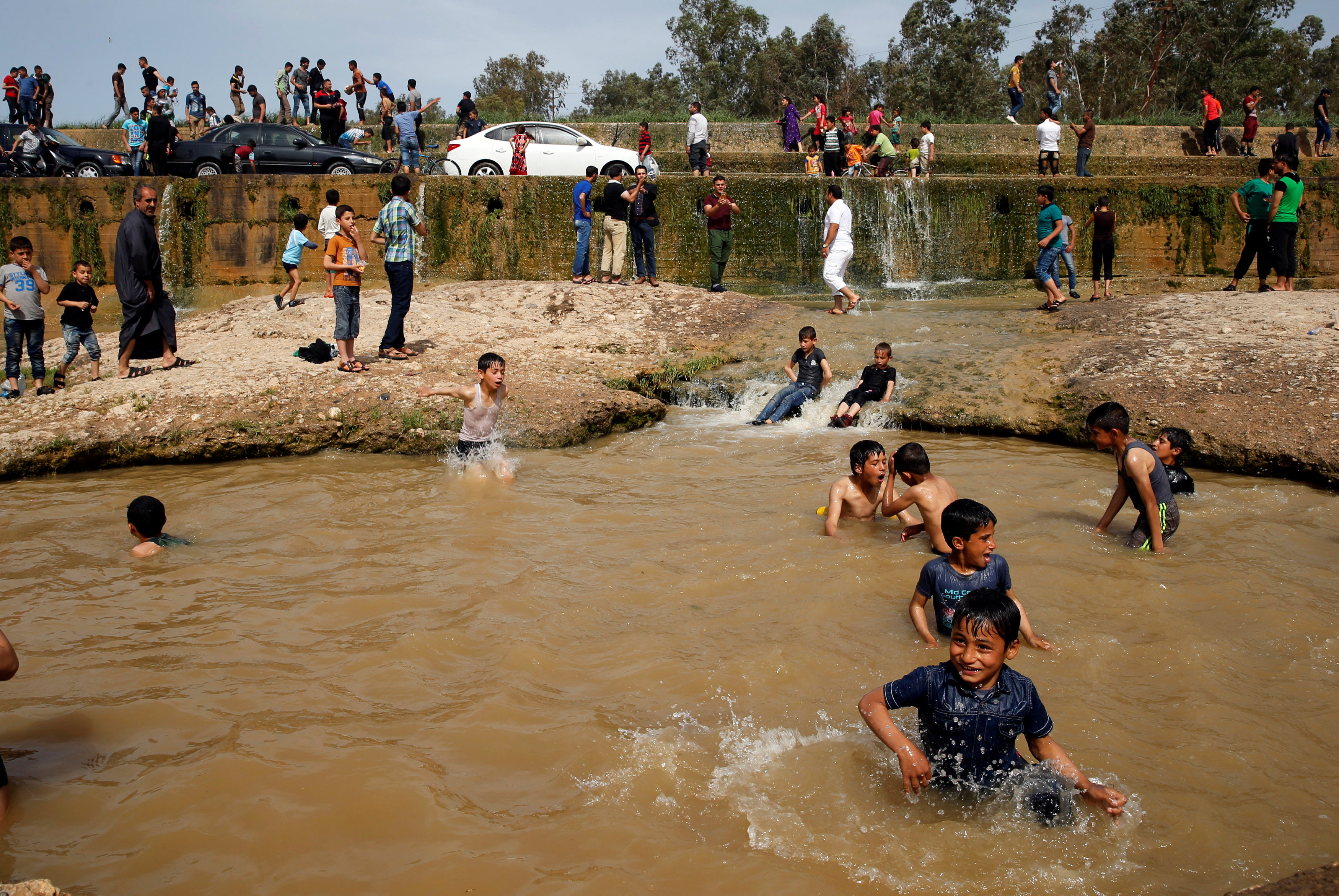 "Iraqi families and youths enjoy their Friday holiday at Shallalat district (Arabic for ""waterfalls"") in eastern Mosul, Iraq, April 21, 2017. REUTERS/ Muhammad Hamed"