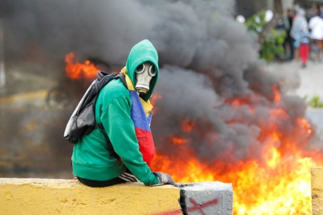 FILE PHOTO: Demonstrator sits next to a fire barricade on a street during a rally against Venezuela's President Nicolas Maduro in Caracas, Venezuela April 24, 2017. REUTERS/Christian Veron/File Photo