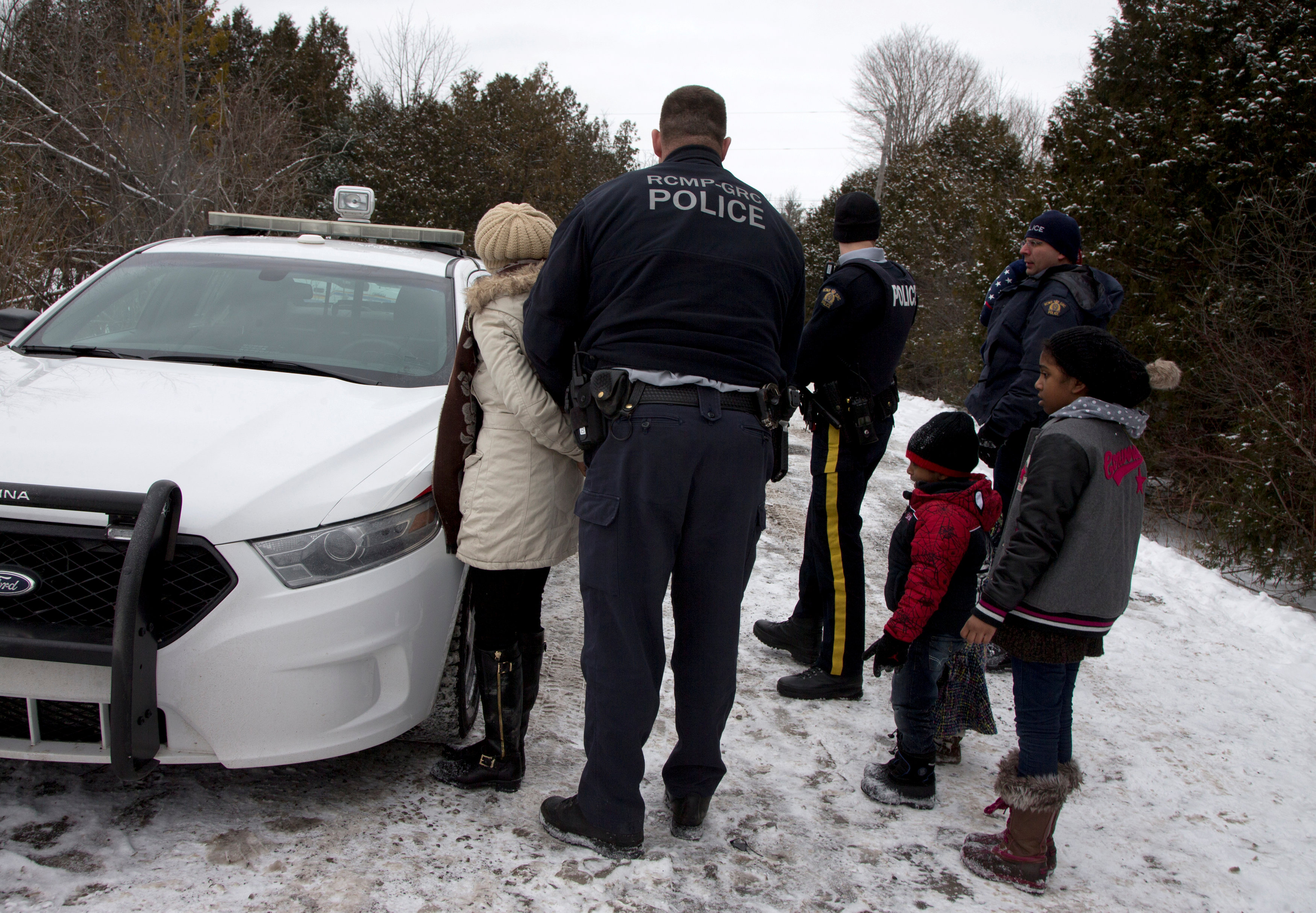FILE PHOTO: A woman who told police that she and her family were from Sudan is taken into custody by Royal Canadian Mounted Police (RCMP) officers after arriving by taxi and walking across the U.S.-Canada border into Hemmingford, Quebec, Canada on February 12, 2017. REUTERS/Christinne Muschi/File Photo