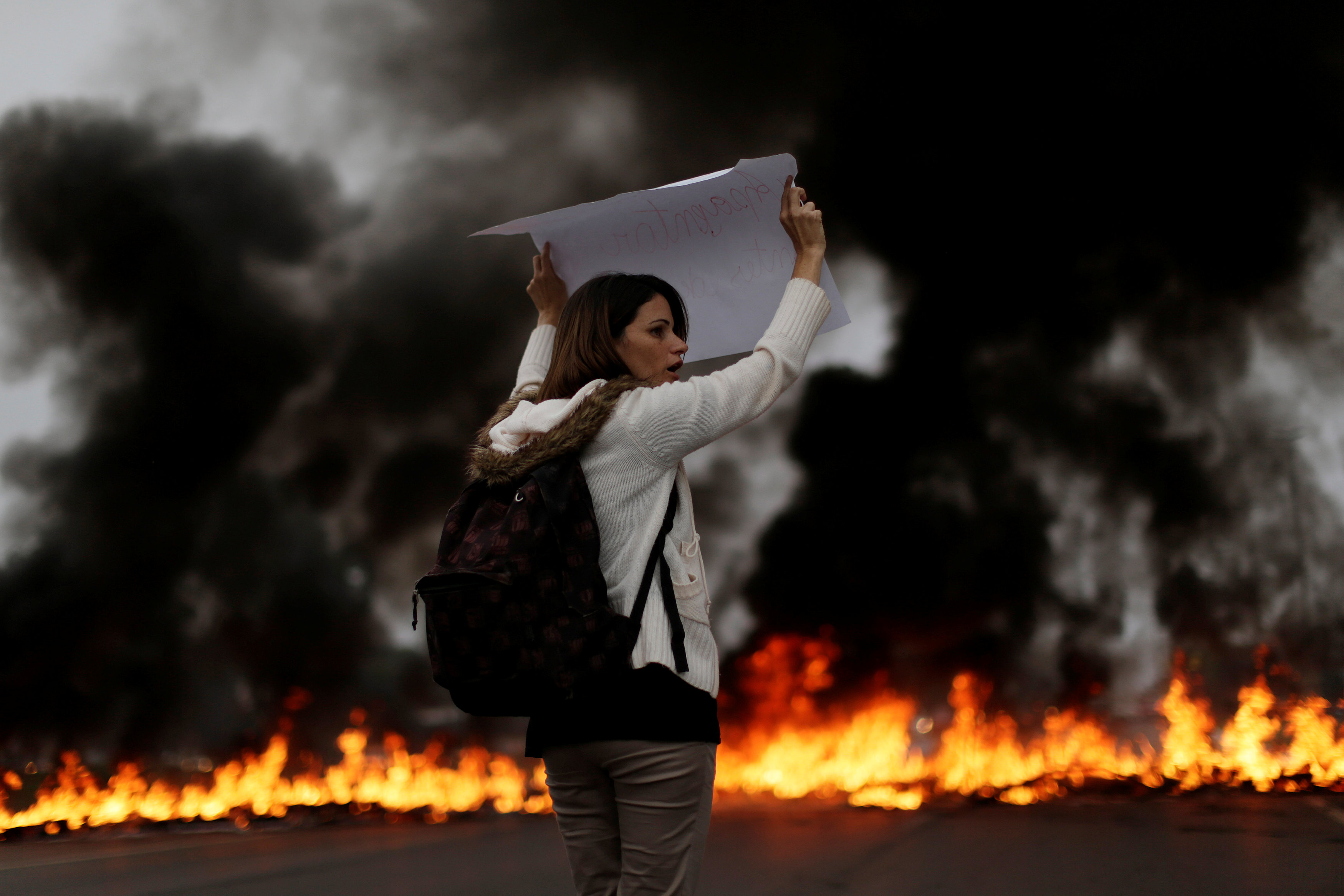 A demonstrators holds a placard in front of a burning barricade during a protest against President Michel Temer's proposal to reform Brazil's social security system in the early hours of general strike in Brasilia, Brazil, April 28, 2017. REUTERS/Ueslei Marcelino