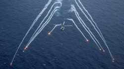 """A U.S. Navy MH-60R Sea Hawk helicopter from the """"Blue Hawks"""" of Helicopter Maritime Strike Squadron 78 fires chaff flares during a training exercise near the aircraft carrier USS Carl Vinson (CVN 70) in the Philippine Sea. U.S. Navy/Mass Communication Specialist 2nd Class Sean M. Castellano/via REUTERS"""