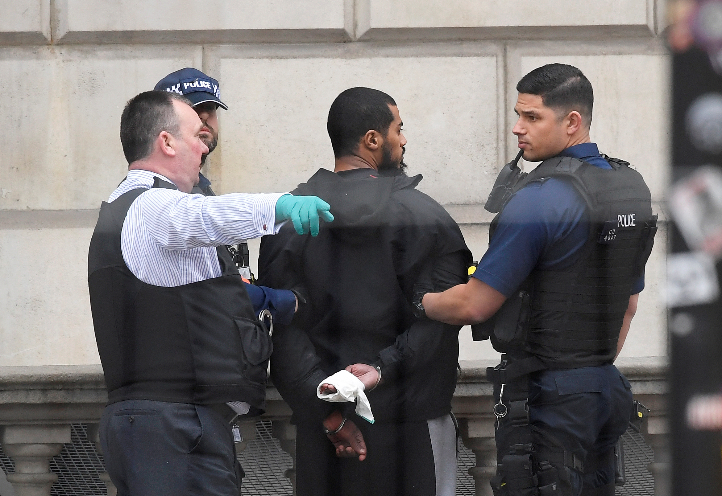 A man is held by police in Westminster after an arrest was made on Whitehall in central London, Britain. REUTERS/Toby Melville