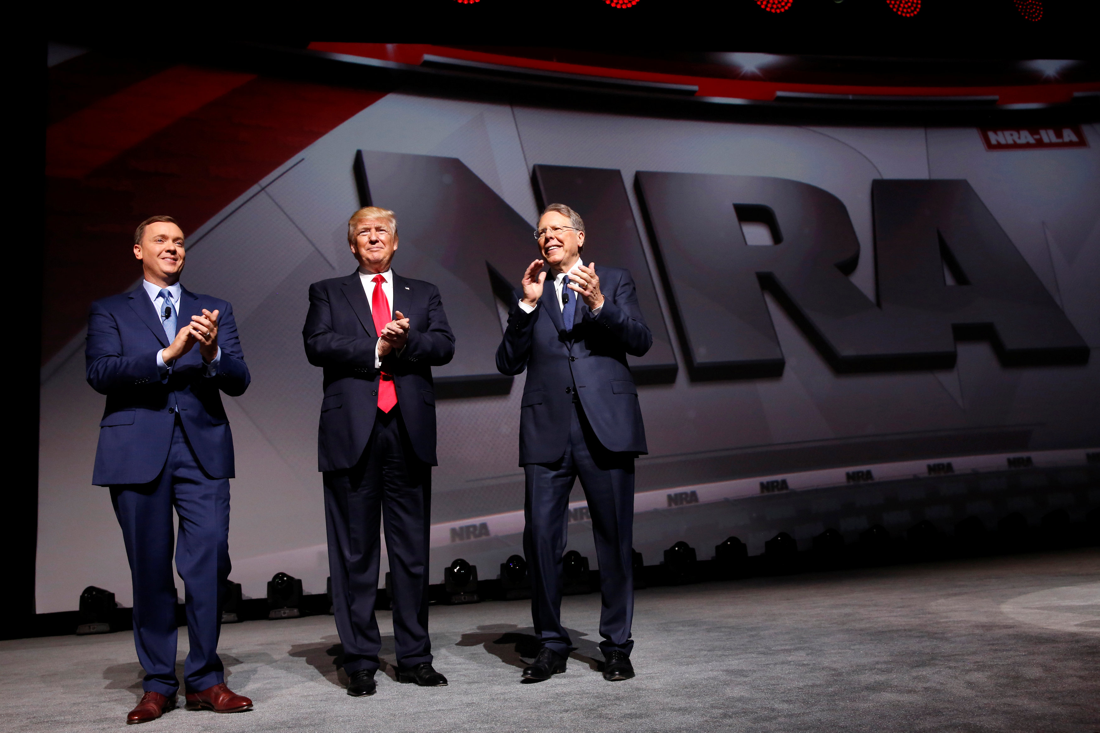 NRA Executive Director Chris Cox (L) and Executive Vice President and CEO Wayne LaPierre (R) welcome U.S. President Donald Trump (C) onstage to deliver remarks at the National Rifle Association (NRA) Leadership Forum at the Georgia World Congress Center in Atlanta, Georgia, U.S., April 28, 2017. REUTERS/Jonathan Ernst