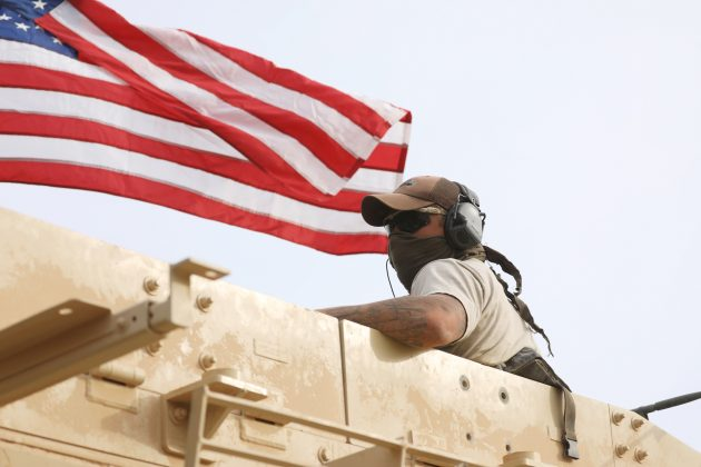 A member of U.S forces rides on a military vehicle in the town of Darbasiya next to the Turkish border, Syria April 28, 2017. REUTERS/Rodi Said