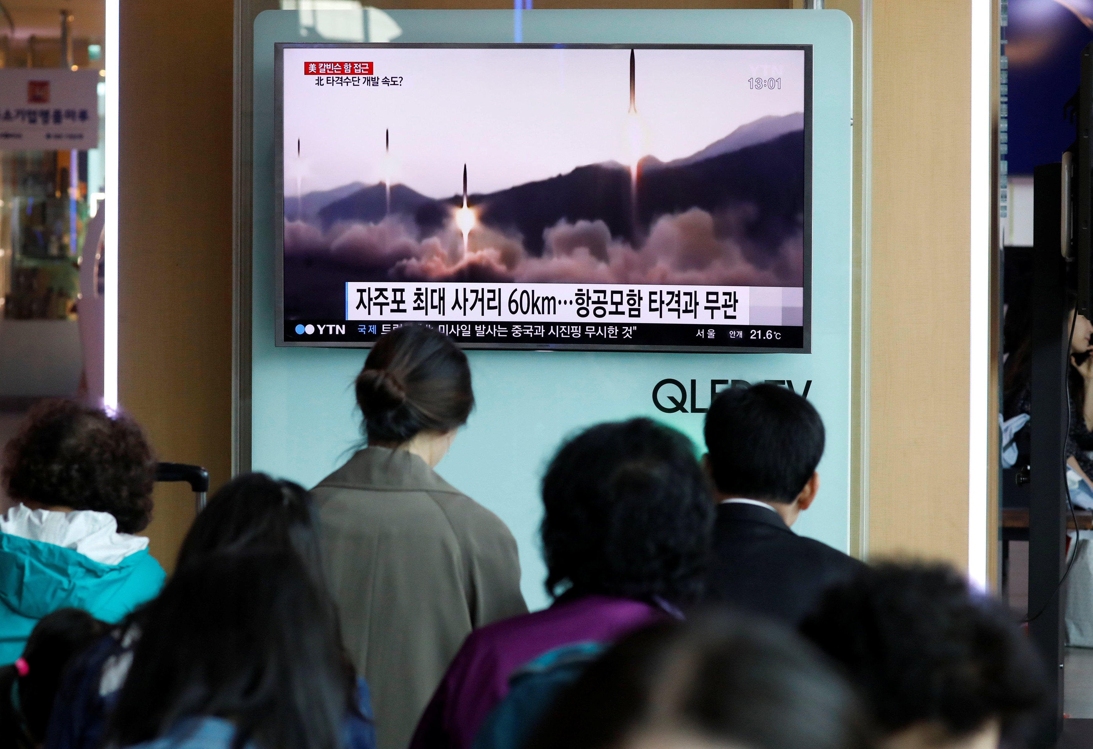 People watch a TV broadcasting of a news report on North Korea's missile launch, at a railway station in Seoul, South Korea.