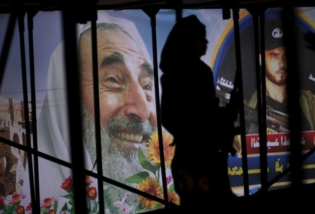 A young Palestinian loyal to Hamas stands under the stage in front of a poster depicting late Hamas spiritual leader Ahmed Yassin (L) during a rally in Khan Younis in the southern Gaza Strip