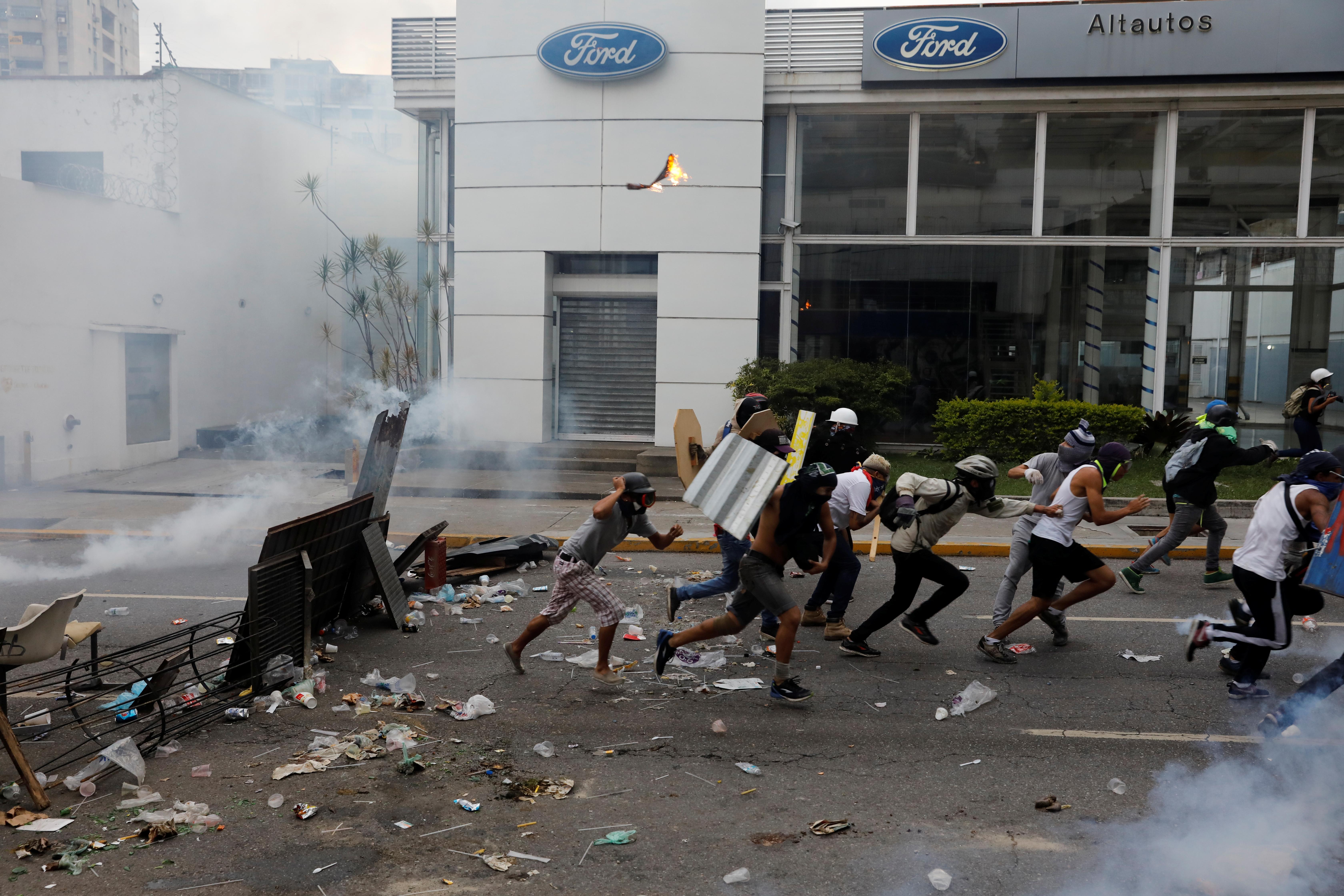 Demonstrators run as they clash with police during a rally against Venezuela's President Nicolas Maduro in Caracas, Venezuela. REUTERS/Carlos Garcia Rawlins