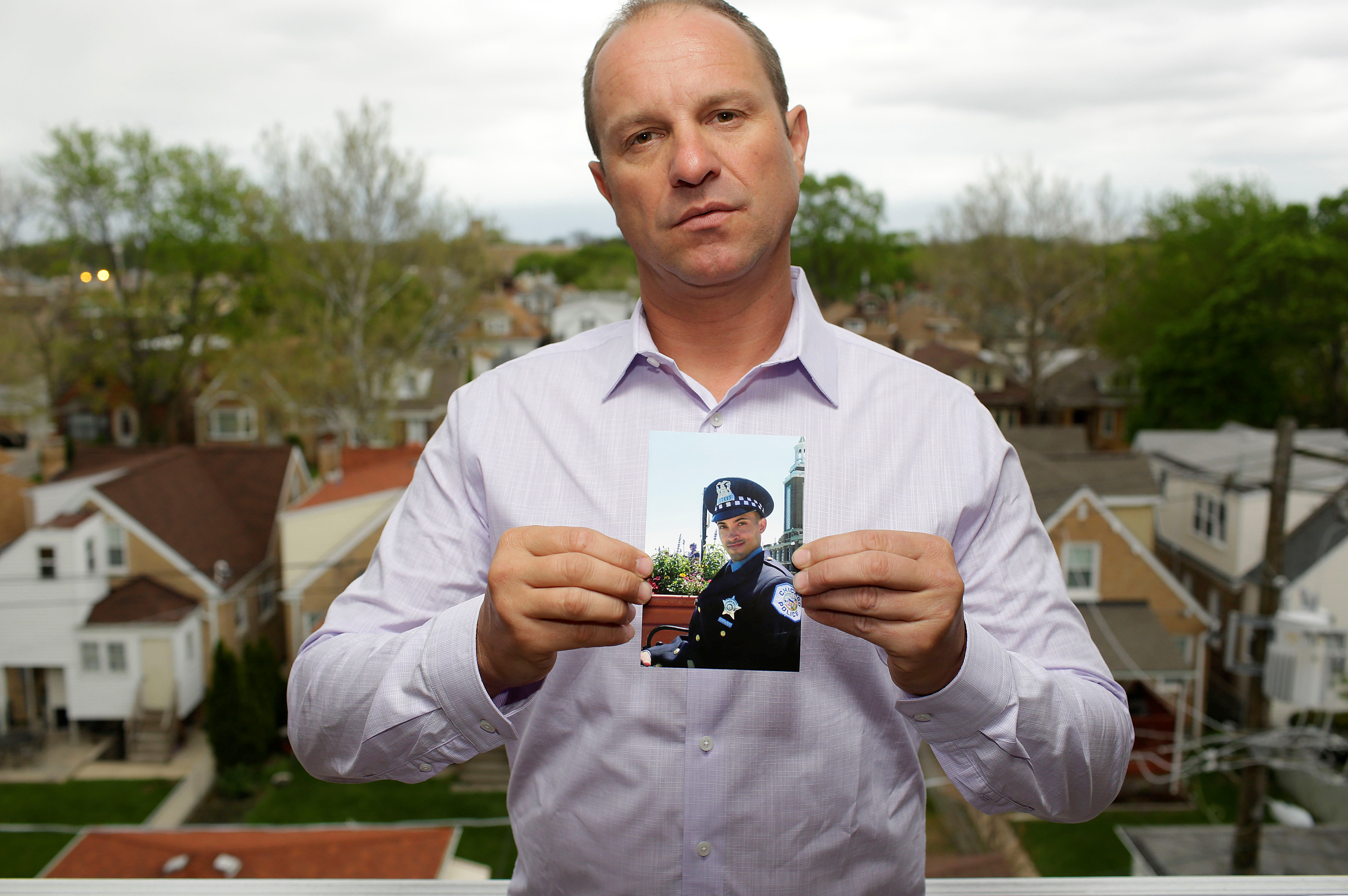 Ark Maciaszek poses with a photo of his cousin, former Chicago police officer and suicide victim Scott Tracz, at his home in Chicago, Illinois, U.S. May 2, 2017. Picture taken May 2, 2017. REUTERS/Joshua Lott
