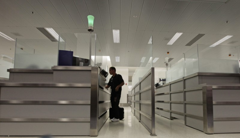 A person stands at the counter of U.S. Immigration upon arriving at Miami airport March 13, 2013. REUTERS/Desmond Boylan