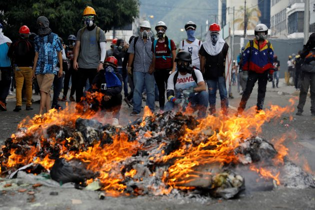 Opposition supporters stand in front of a fire during clashes with riot police at a rally against President Nicolas Maduro in Caracas, Venezuela May 3, 2017. REUTERS/Carlos Garcia Rawlins