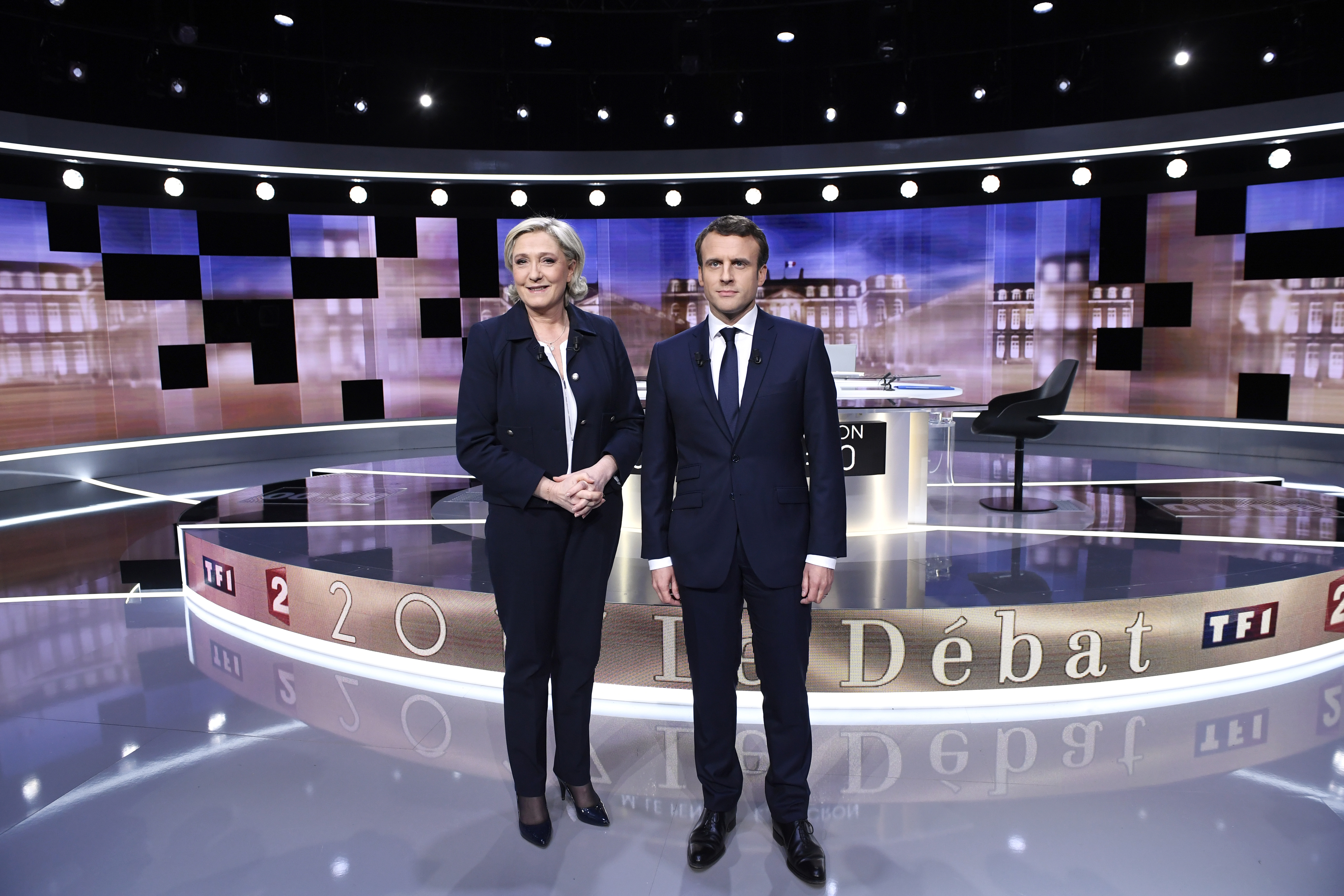 Candidates for the 2017 presidential election, Emmanuel Macron (R), head of the political movement En Marche !, or Onwards !, and Marine Le Pen, of the French National Front (FN) party, pose prior to the start of a live prime-time debate in the studios of French television station France 2, and French private station TF1 in La Plaine-Saint-Denis, near Paris. REUTERS/Eric Feferberg/Pool