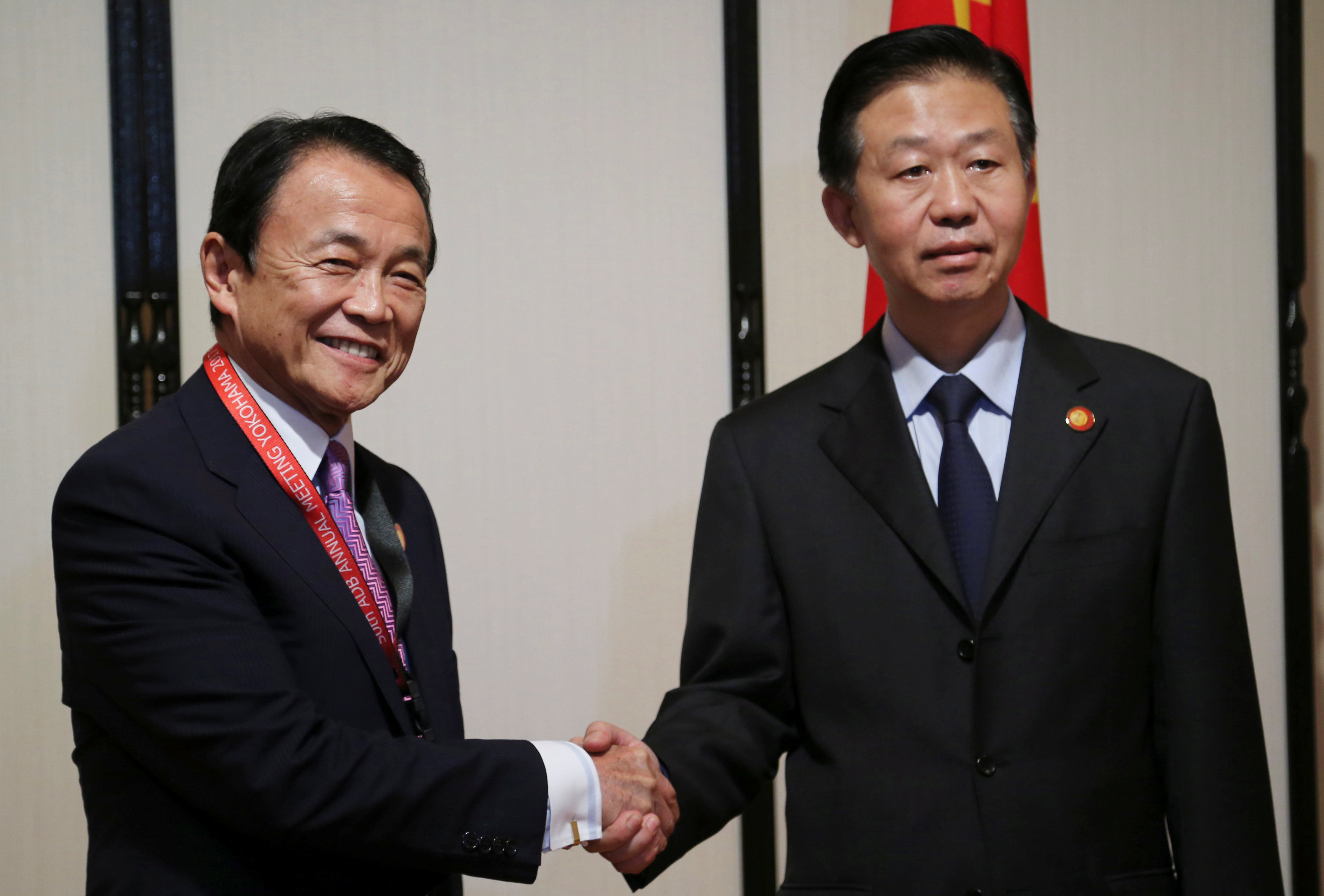 Chinese Finance Minister Xiao Jie (R) and Japanese Finance Minister Taro Aso shake hands during their bilateral meeting, on the sidelines of Asian Development Bank (ADB) annual meeting, in Yokohama, Japan, Saturday, May 6, 2017. REUTERS/Koji Sasahara/Pool
