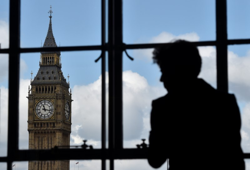 A woman looks out of a window at the Big Ben clock tower in London, Britain,
