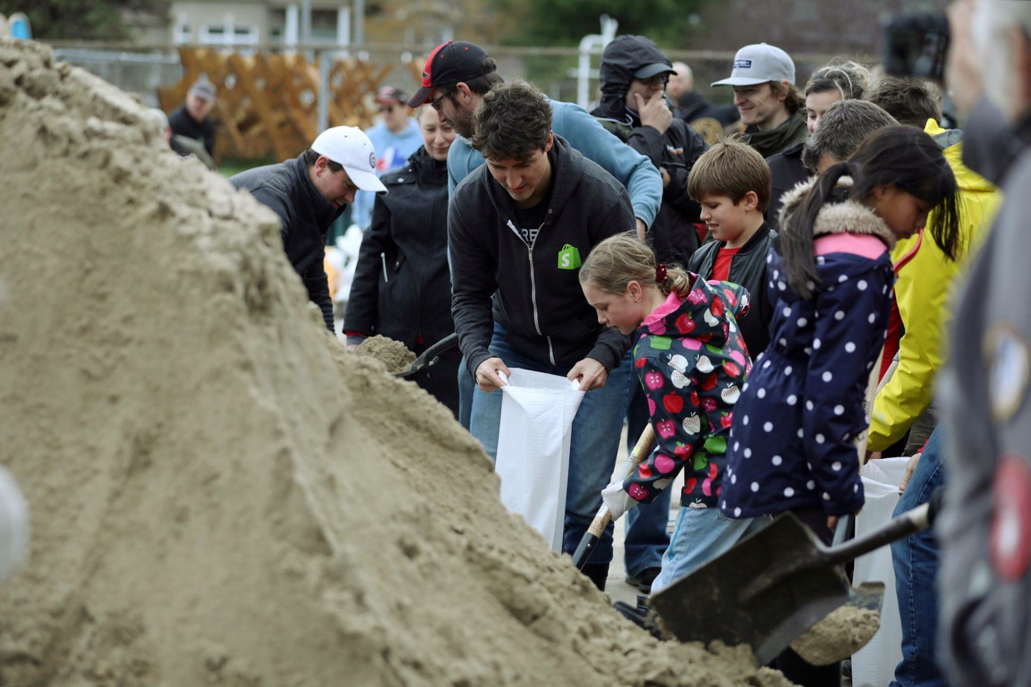 Canada's Prime Minister Justin Trudeau (C) helps fill sandbags after flooding in Terrasse-Vaudreuil, Quebec