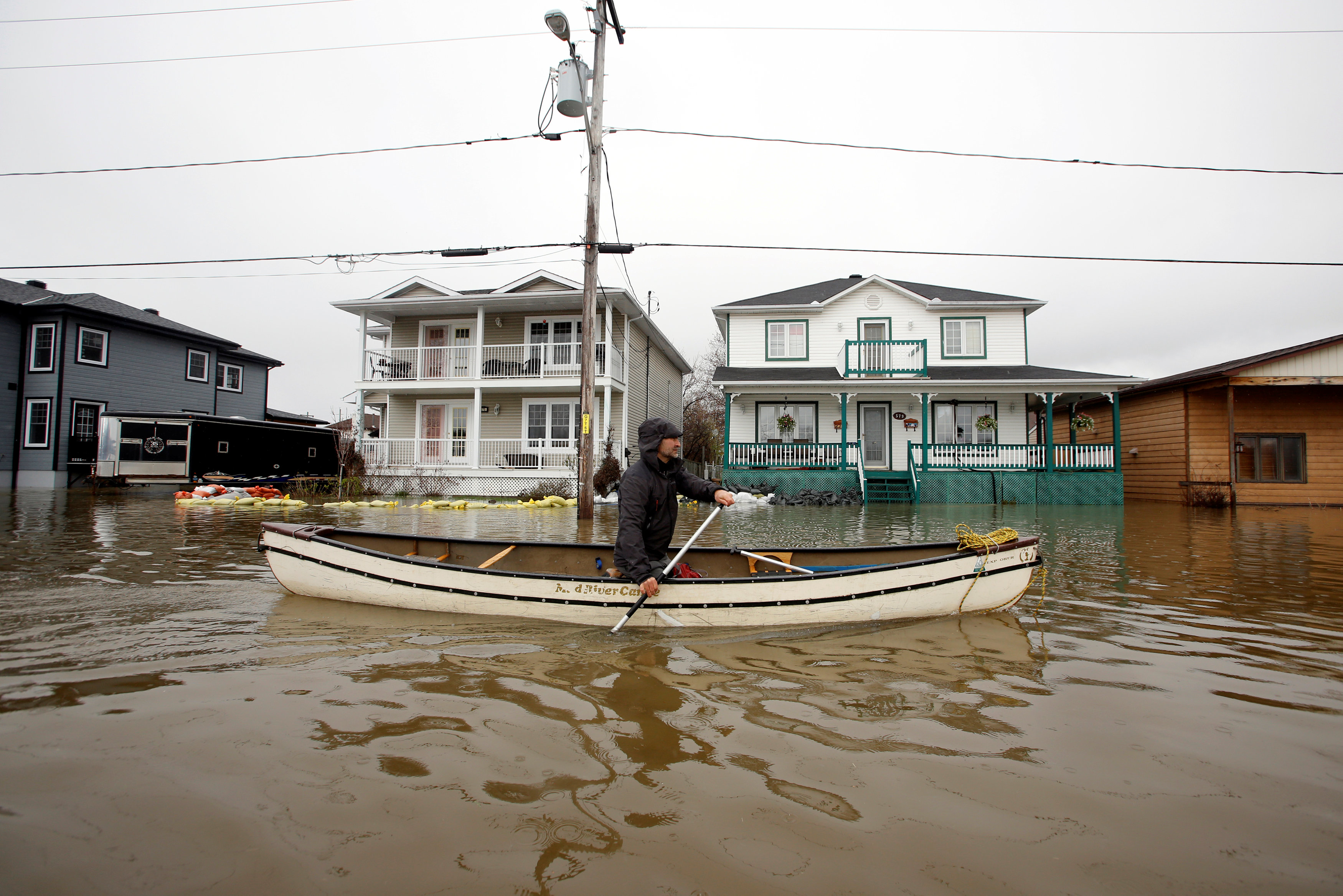 A man paddles a canoe in a flooded residential area in Gatineau, Quebec, Canada