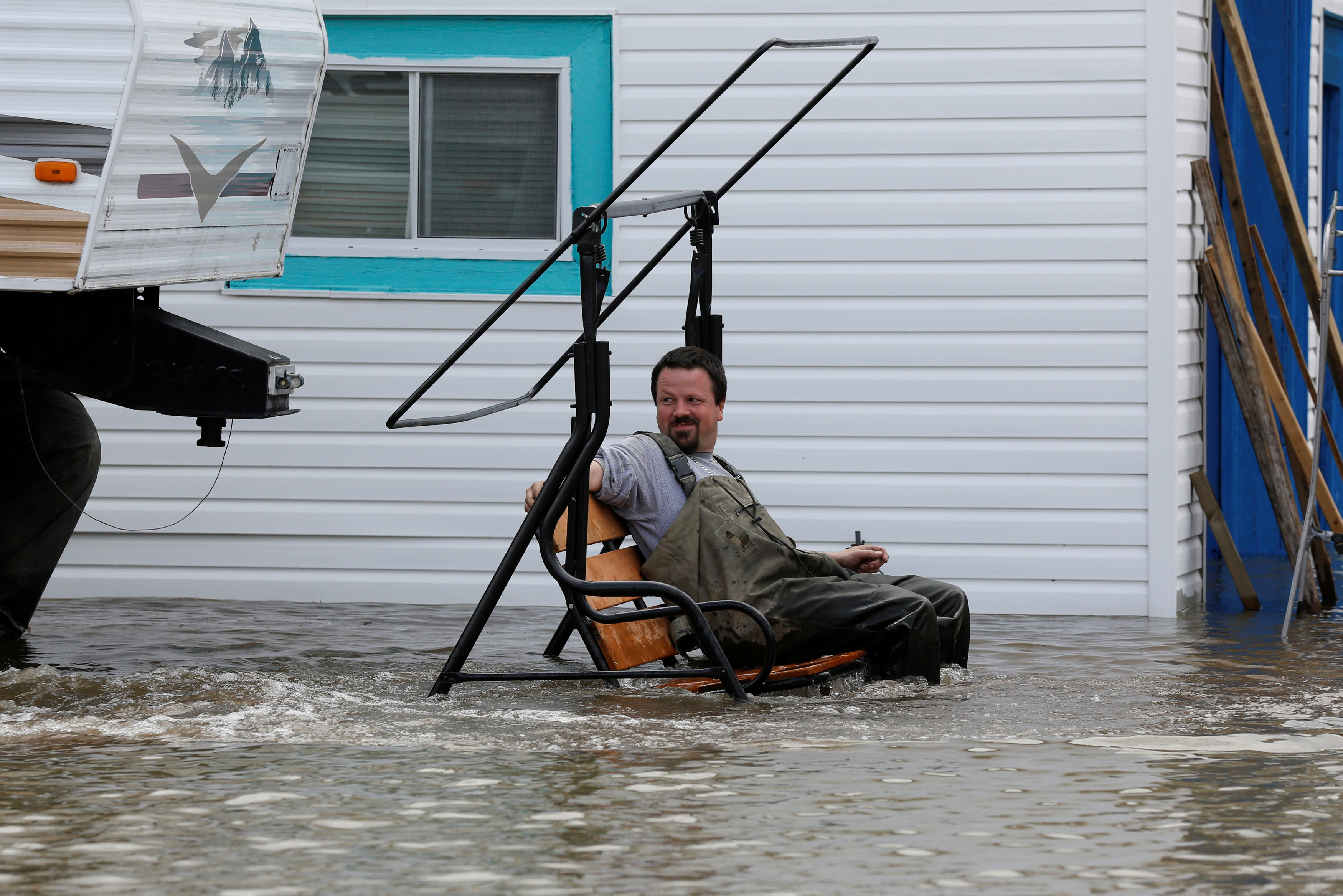 A resident sits on a swing in a flooded residential area in Rigaud, Quebec, Canada