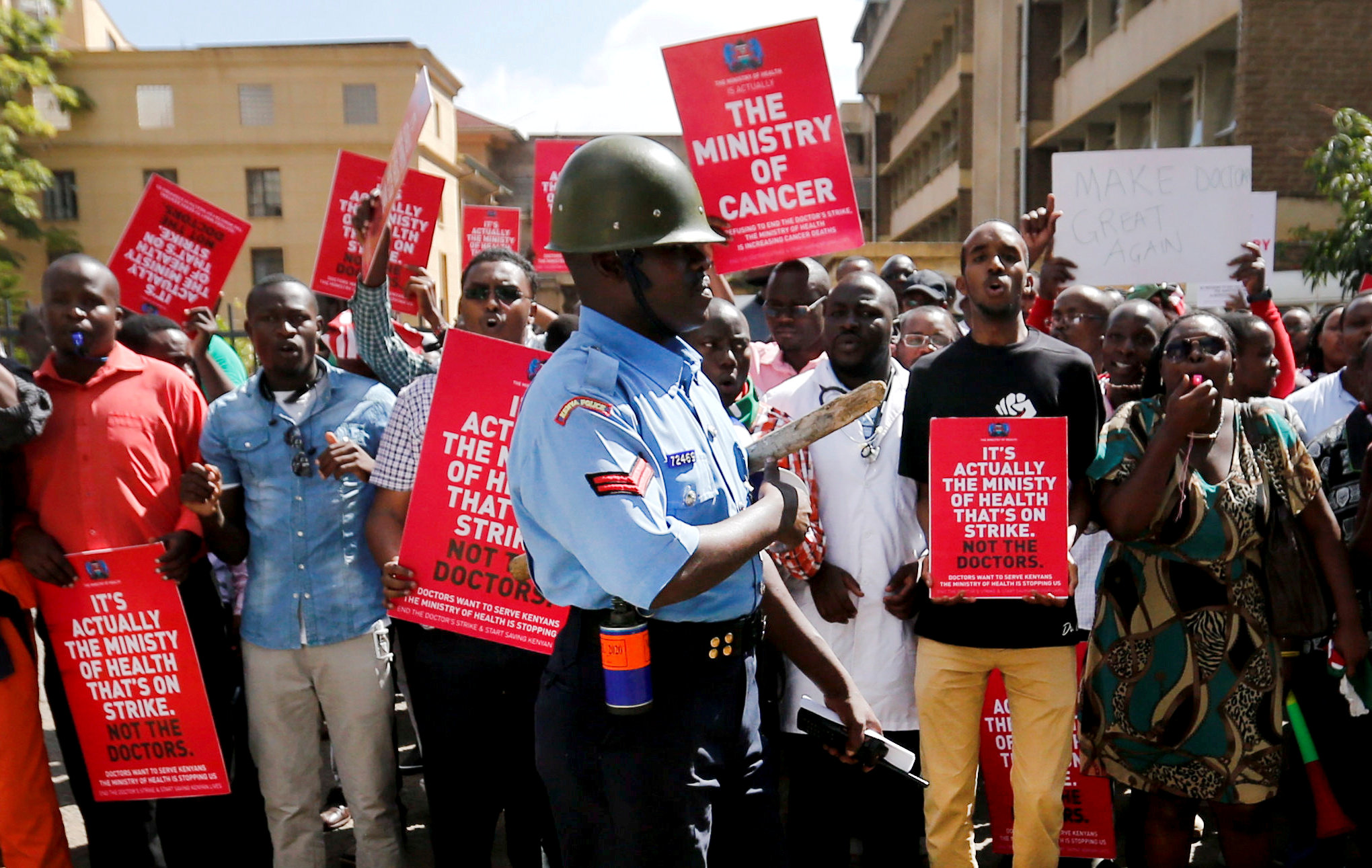 FILE PHOTO: A riot policeman stands guard as doctors chant slogans after their case to demand fulfilment of a 2013 agreement between their union and the government that would raise their pay and improve working conditions, was heard at the employment and labour relations courts in Nairobi, Kenya, February 13, 2017. REUTERS/Thomas Mukoya/File Photo