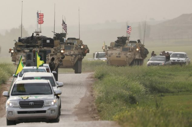 FILE PHOTO: Kurdish fighters from the People's Protection Units (YPG) head a convoy of U.S military vehicles in the town of Darbasiya next to the Turkish border, Syria April 28, 2017. REUTERS/Rodi Said/File Photo