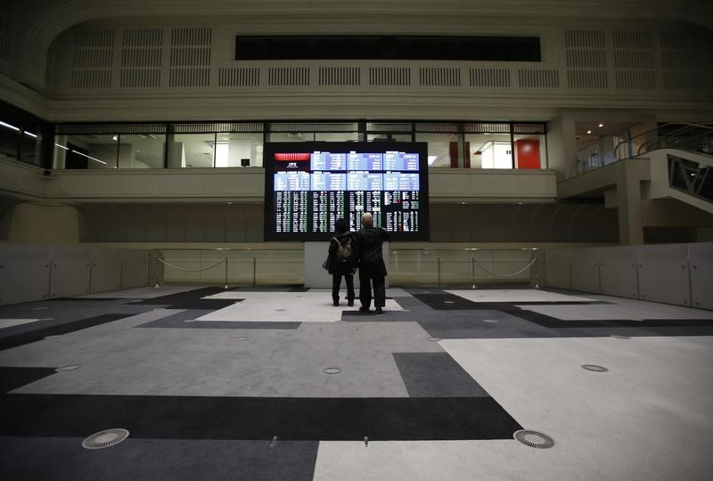 FILE PHOTO: Visitors looks at an electronic board showing the Japan's Nikkei average at the Tokyo Stock Exchange (TSE) in Tokyo, Japan, February 9, 2016. REUTERS/Issei Kato/Files