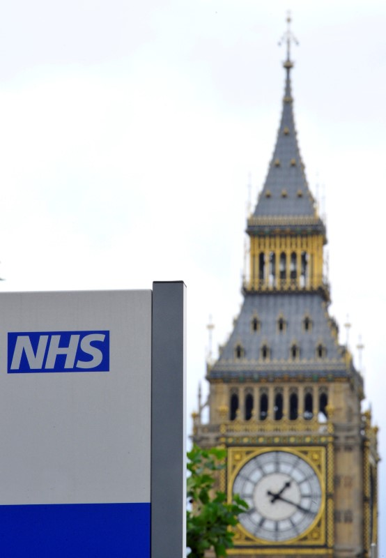 FILE PHOTO: A National Health Service (NHS) sign is seen in the grounds of St Thomas' Hospital, in front of the Houses of Parliament in London June 7, 2011. REUTERS/Toby Melville/File Photo