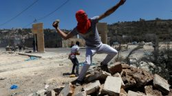 A Palestinian protester hurls stones towards Israeli troops during clashes in the West Bank village of Beita, near Nablus May 12, 2017. REUTERS/Mohamad Torokman