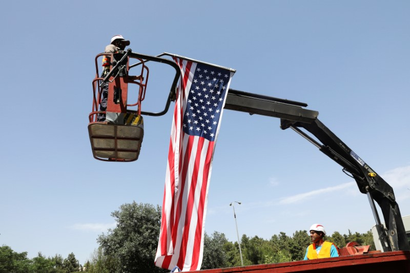 A labourer stands on a crane as he hangs an American flag to a street post, in preparation for the upcoming visit of U.S. President Donald Trump to Israel, in Jerusalem May 18, 2017. REUTERS/Ronen Zvulun