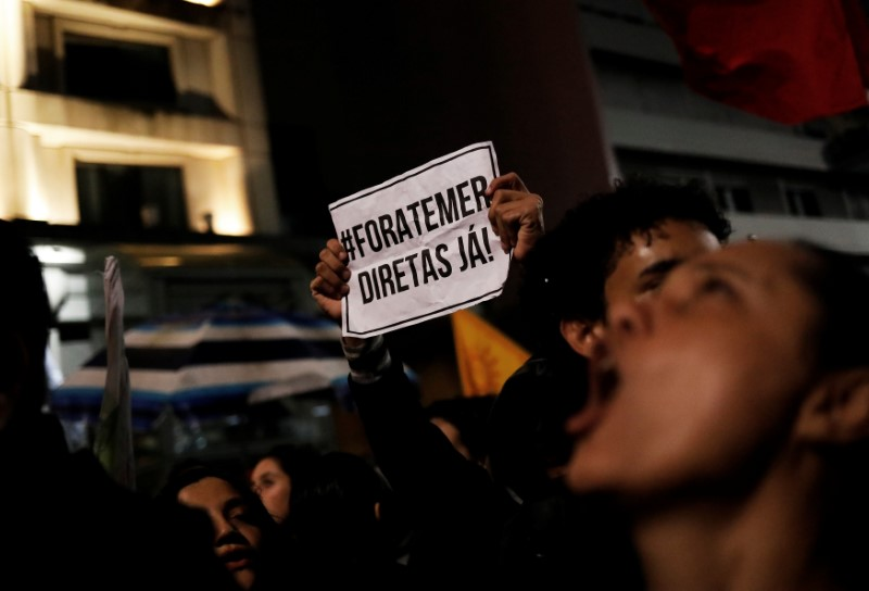 """Demonstrators shout slogans during a protest against Brazil's President Michel Temer in Sao Paulo, Brazil, May 18, 2017. The sign reads """"Out Temer and Elections now!."""" REUTERS/Nacho Doce"""
