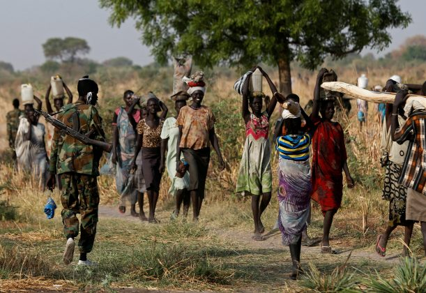 FILE PHOTO: A soldier walks past women carrying their belongings near Bentiu, northern South Sudan, February 11, 2017. REUTERS/Siegfried Modola /File Photo