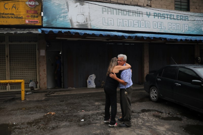 Manuel Fernandes, a local businessman, embraces a neighbour outside of his bread and cake shop after looters broke in, following days of protest against Venezuelan President Nicolas Maduro in the city of Los Teques, near Caracas, Venezuela, May 19, 2017. REUTERS/Carlos Barria