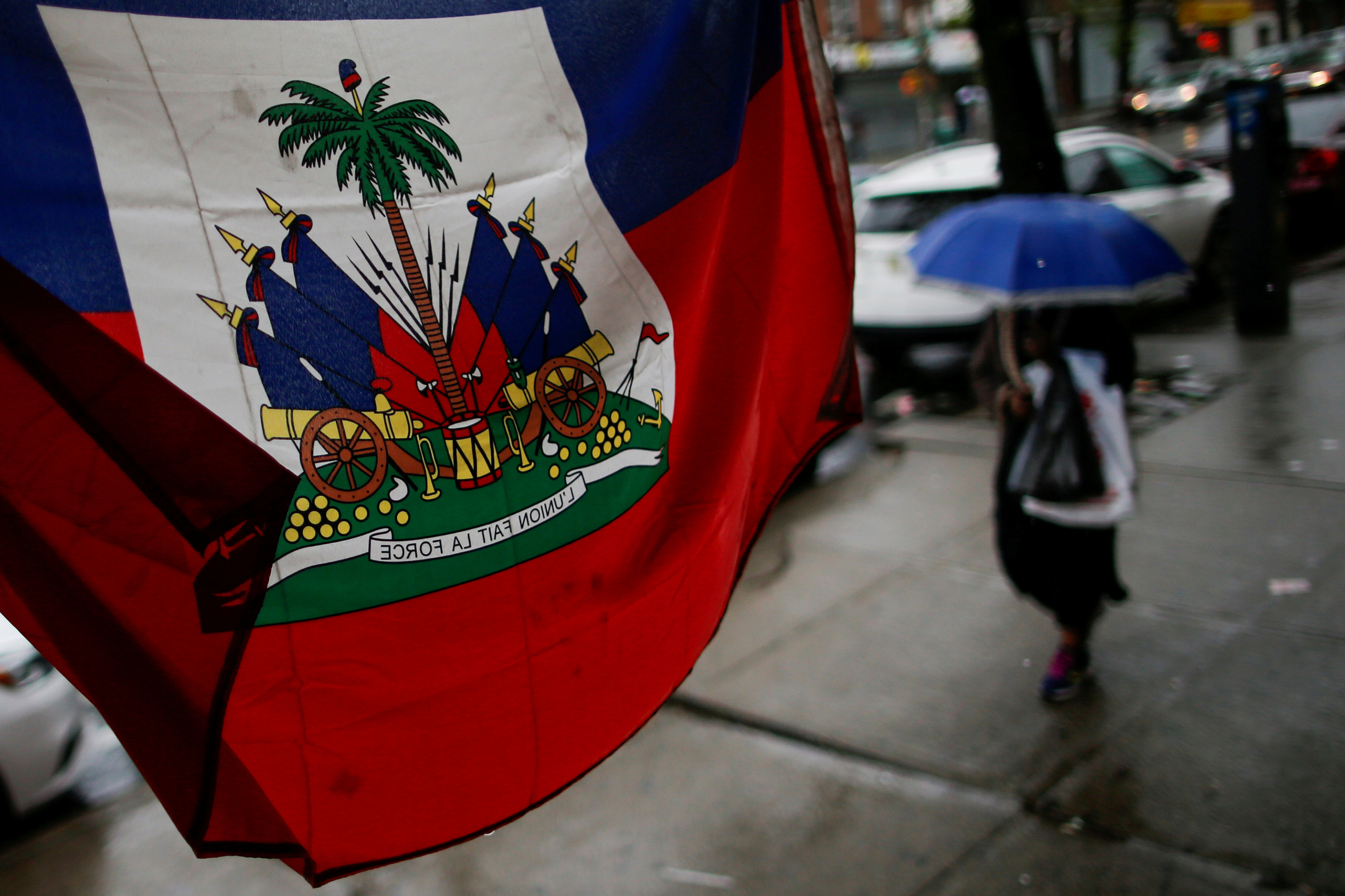 FILE PHOTO: A Flag from Haiti is pictured in a local store as a woman walks under rain at the neighborhood of Brooklyn in New York, U.S. May 13, 2017. REUTERS/Eduardo Munoz/File Photo