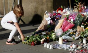 A girl leaves flowers for the victims of an attack on concert goers at Manchester Arena, in central Manchester, Britain May 23, 2017. REUTERS/Peter Nicholls