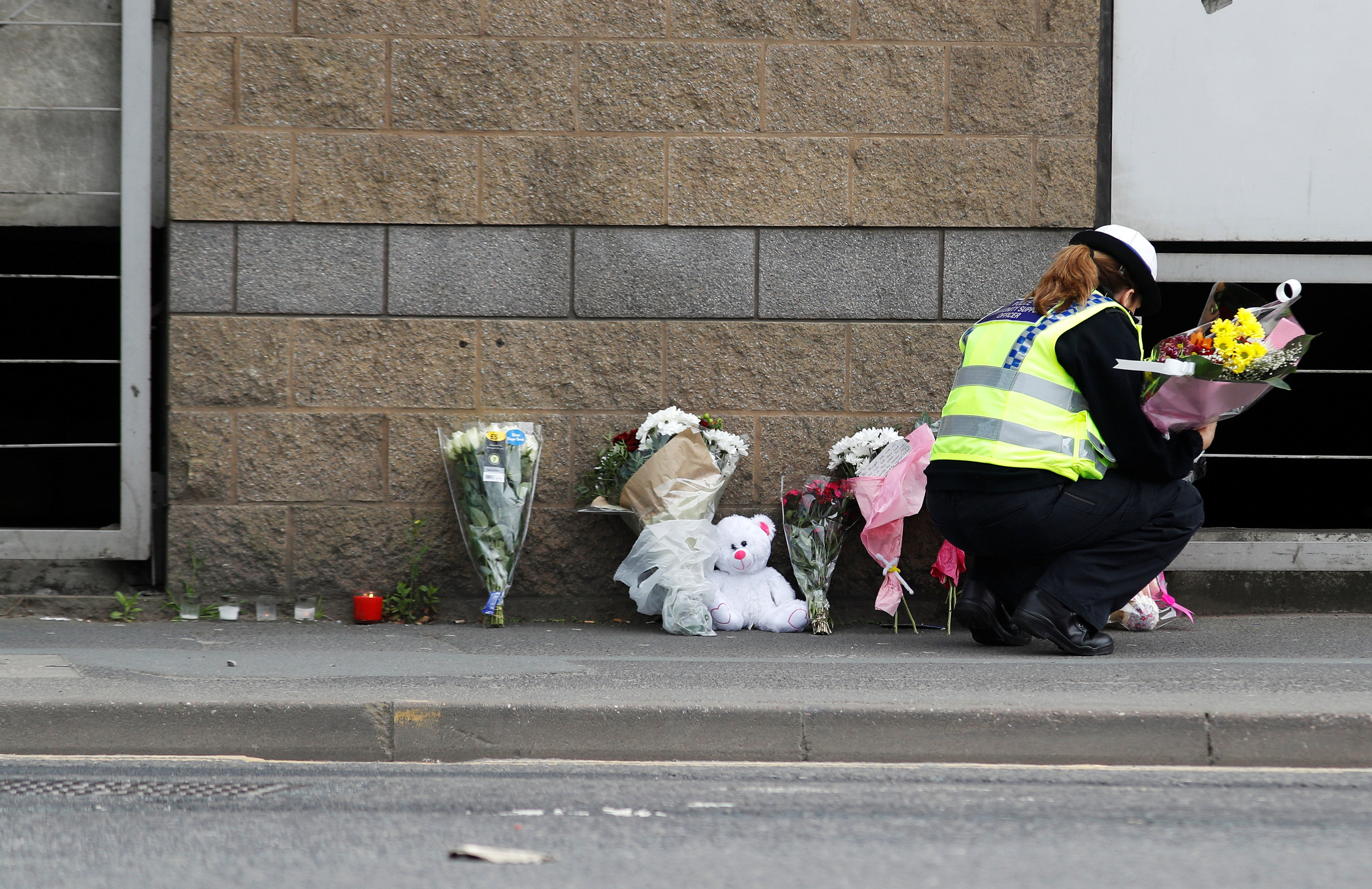 A community support officer places flowers near Manchester Arena in Manchester, Britain May 24, 2017. REUTERS/Peter Nicholls