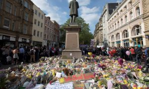 Messages and floral tributes left for the victims of the attack on Manchester Arena lie around the statue in St Ann's Square in central Manchester, May 24, 2017. REUTERS/Jon Super