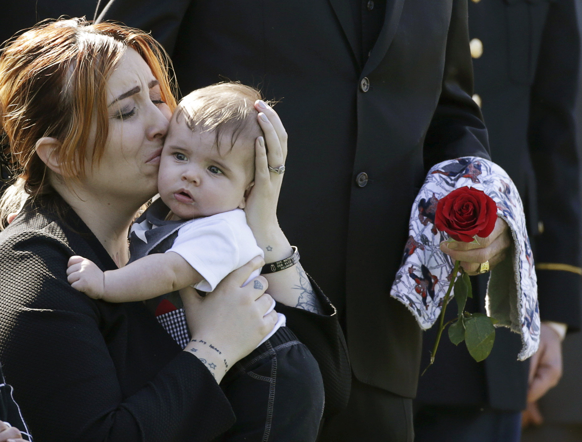 FILE PHOTO: Widow Alexandra McClintock holds her son Declan during a burial service for her husband, U.S. Army Sergeant First Class Matthew McClintock, who was killed in action in January at Arlington National Cemetery in Virginia March 7, 2016. REUTERS/Gary Cameron/File Photo