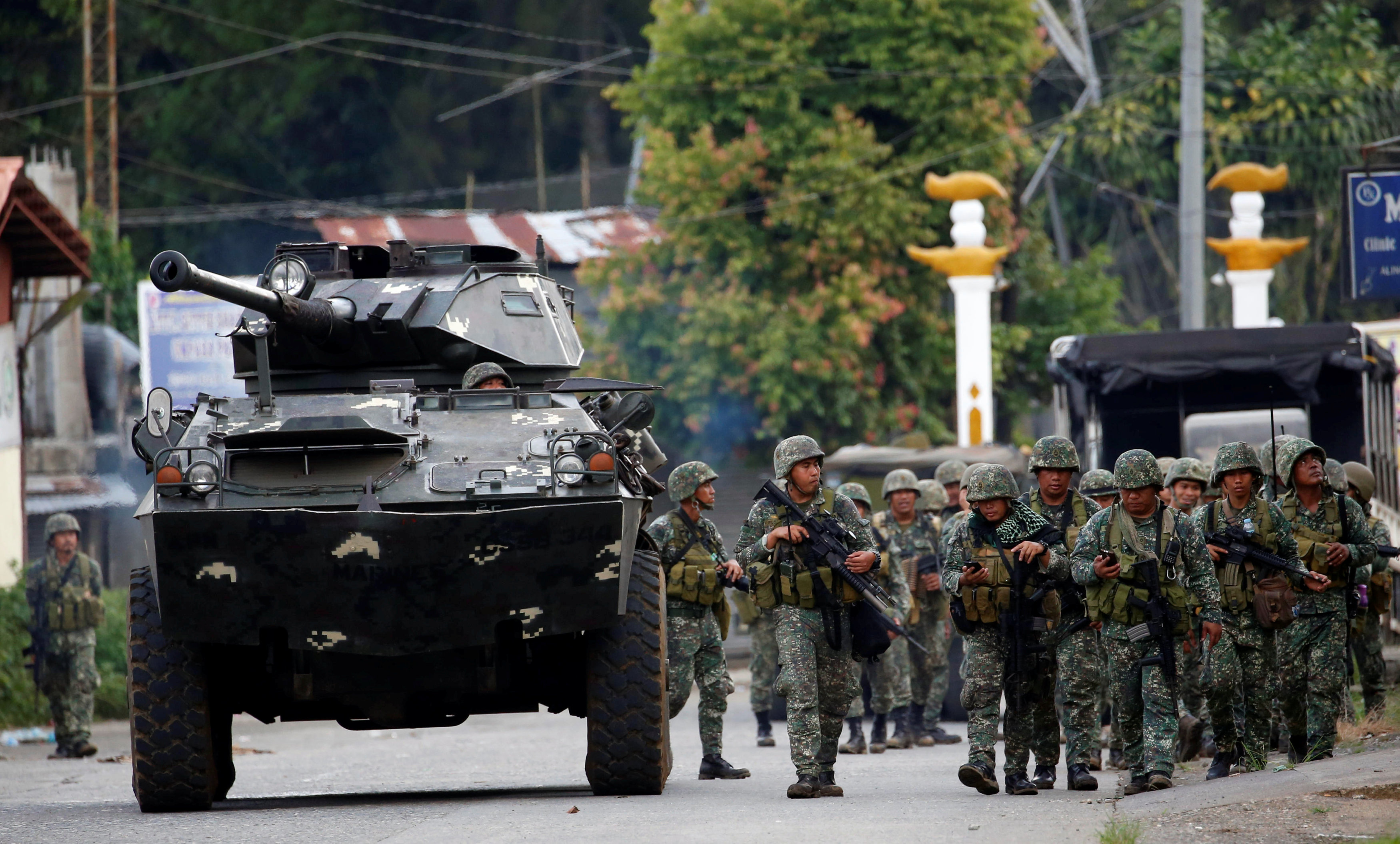 Members of Philippine Marines walk next to an armoured fighting vehicle (AFV) as they advance their position in Marawi City, Philippines May 28