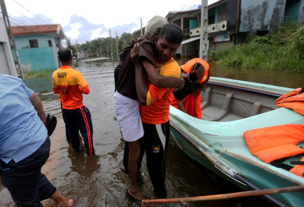 A Sri Lankan Navy rescue team member carries an old man on a flooded road during a rescue mission in Nagoda village in Kalutara, Sri Lanka May