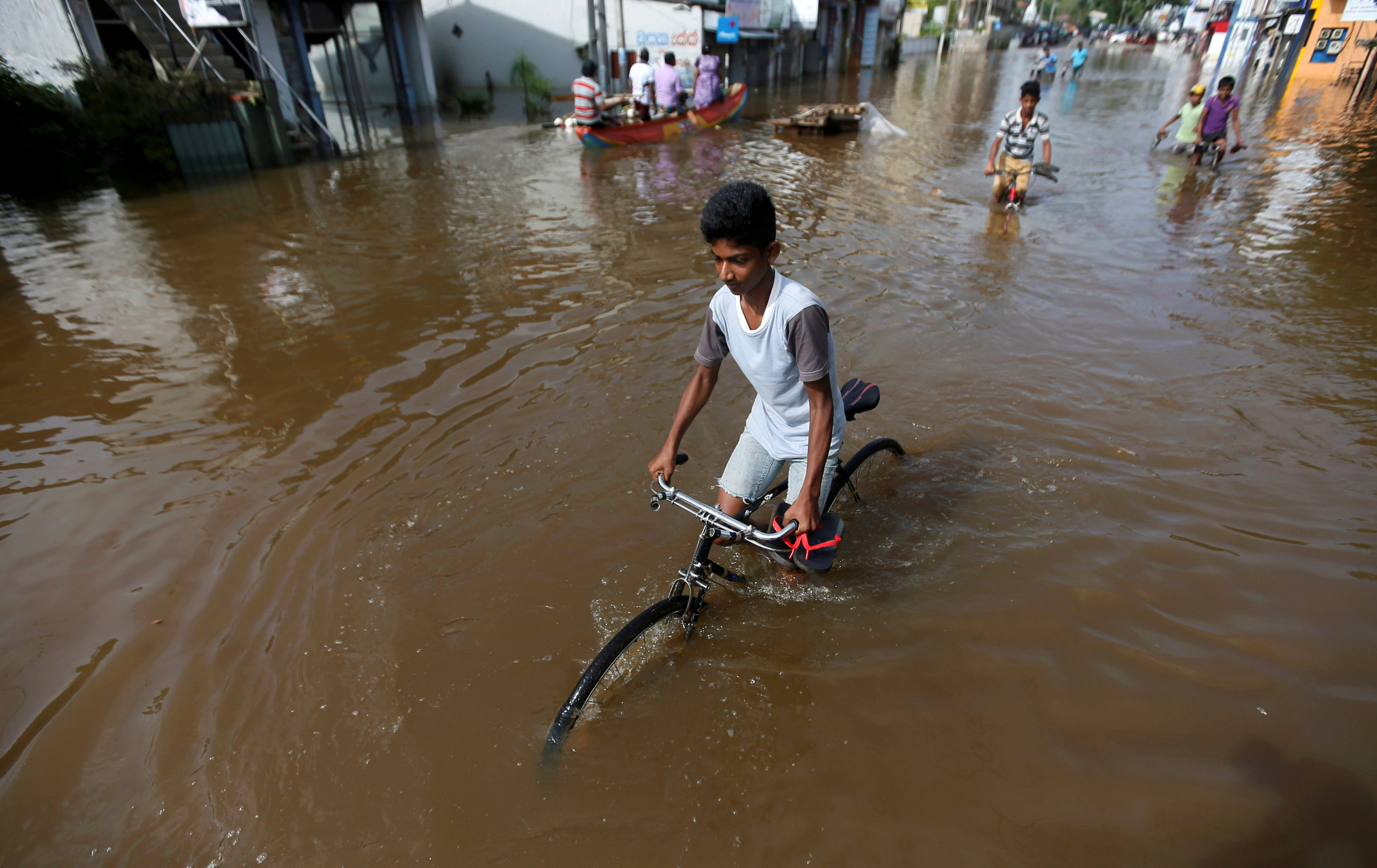 A boy rides his bike along a flooded road in Nagoda village, in Kalutara, Sri Lanka May 29, 2017.