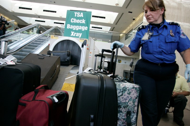 A TSA worker loads suitcases at the checked luggage security screening station at Los Angeles International Airport in Los Angeles, California,