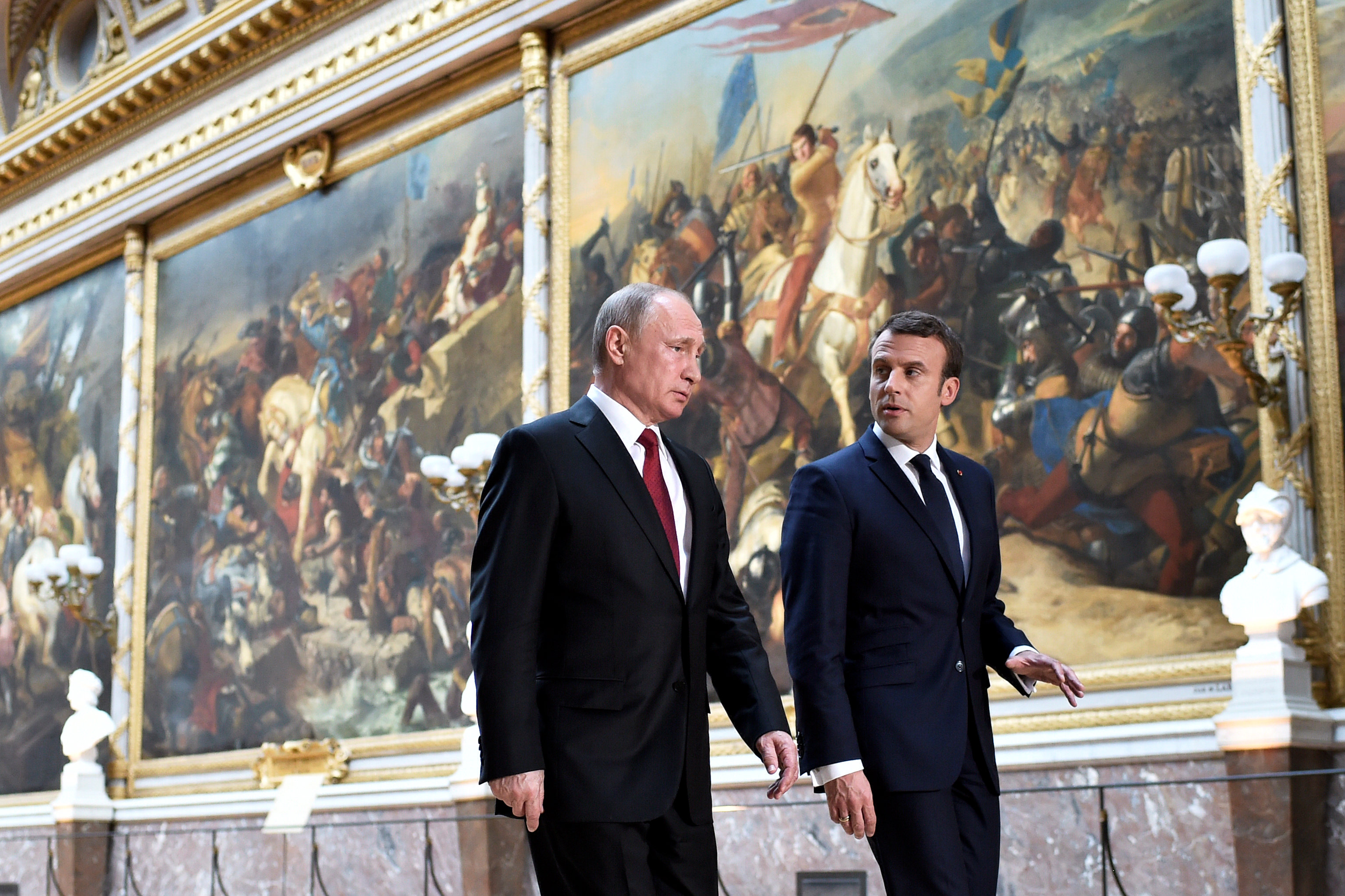 French President Emmanuel Macron (R) speaks to Russian President Vladimir Putin (L) in the Galerie des Batailles (Gallery of Battles) as they arrive for a joint press conference at the Chateau de Versailles before the opening of an exhibition marking 300 years of diplomatic ties between the two countries in Versailles, France, May 29, 2017.