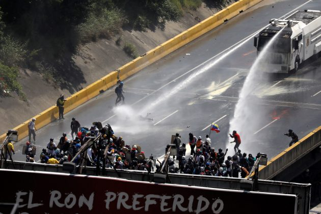 "Riot security forces release jets of water from their water cannon on demonstrators during riots at a march to the state Ombudsman's office in Caracas, Venezuela May 29, 2017. The banner reads ""The favorite Ron"". REUTERS/Carlos Garcia Rawlins"