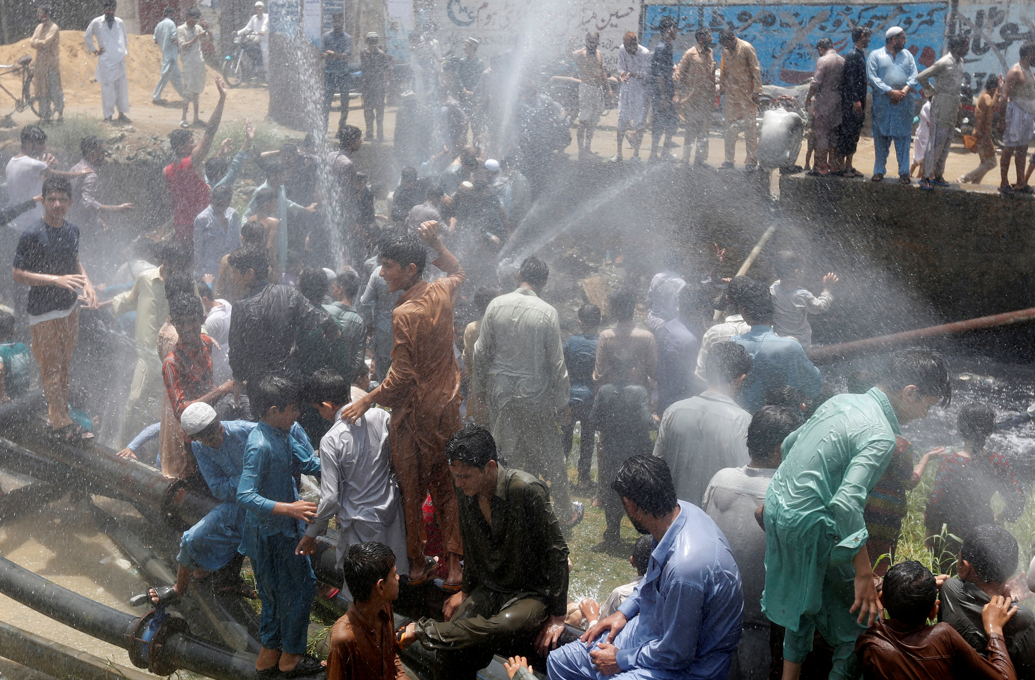 People cool off with water from water lines after they punctured them in protest against the power outages in their area in Karachi, Pakistan May 30, 2017. REUTERS/Akhtar Soomro